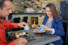 Couples mangeant des sushi dans le restaurant Images stock