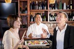 Couples mangeant des sushi dans le restaurant japonais Photos stock