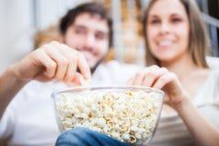 Couples mangeant du maïs éclaté tout en observant un film Photos libres de droits
