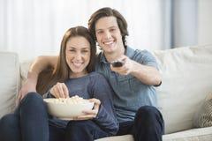 Couples mangeant du maïs éclaté tout en regardant la TV Photographie stock libre de droits