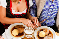 Couples mangeant du rôti de porc dans le restaurant bavarois Photographie stock libre de droits
