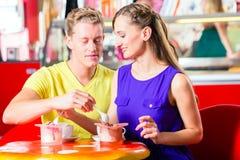 Couples mangeant la crème glacée en café Image stock