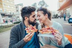 Couples mangeant la pizza dehors et le sourire Photos libres de droits