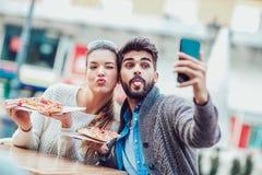 Couples mangeant la pizza dehors et le sourire Image libre de droits