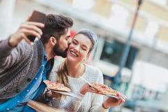 Couples mangeant la pizza dehors et le sourire Images stock