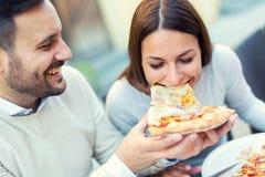 Couples mangeant le casse-croûte de pizza dehors Images libres de droits