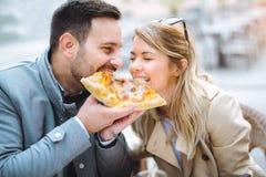 Couples mangeant le casse-croûte de pizza dehors Image stock