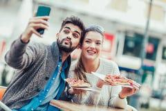 Couples mangeant le casse-croûte de pizza dehors Photos libres de droits