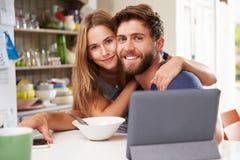 Couples mangeant le petit déjeuner utilisant la Tablette et le téléphone de Digital Photographie stock libre de droits