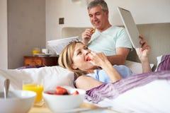 Couples mangeant le petit déjeuner dans le lit avec la Tablette de papier et de Digital Photos libres de droits