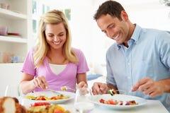Couples mangeant le repas à la maison ensemble photos stock