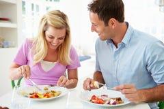Couples mangeant le repas à la maison ensemble photo stock