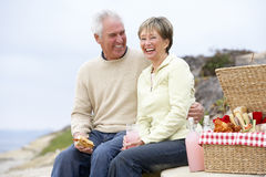 Couples mangeant un repas de fresque d'Al à la plage Photos stock