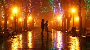 Couples marchant à la ruelle dans des lumières de nuit Photographie stock libre de droits
