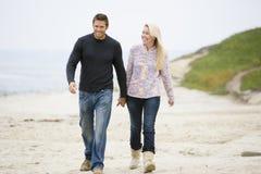 Couples marchant aux mains de fixation de plage Photo stock