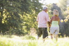 Couples marchant dans des mains de fixation de stationnement Images stock