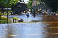 Couples marchant dans l'eau en inondation Photographie stock libre de droits