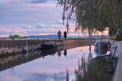 Couples marchant dans le coucher du soleil d'automne marchant par un canal avec des bateaux image stock