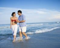 Couples marchant dans les ondes. Photographie stock