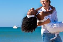 Couples marchant et fonctionnant sur la plage Photo stock