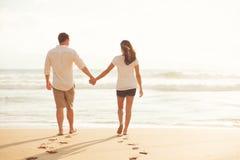 Couples marchant le long de l'océan au coucher du soleil Images stock