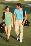 Couples marchant le long du terrain de golf Photographie stock libre de droits