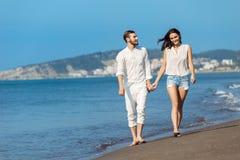 Couples marchant par Heron Jeunes couples interraciaux heureux marchant sur se retenir de sourire de plage autour de l'un l'autre Photo stock