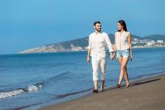 Couples marchant par Heron Jeunes couples interraciaux heureux marchant sur se retenir de sourire de plage autour de l'un l'autre Image stock