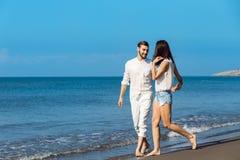 Couples marchant par Heron Jeunes couples interraciaux heureux marchant sur se retenir de sourire de plage autour de l'un l'autre Photo libre de droits