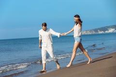 Couples marchant par Heron Jeunes couples interraciaux heureux marchant sur se retenir de sourire de plage autour de l'un l'autre Photos stock