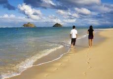 Couples marchant par le bord de l'eau Image stock