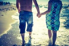 Couples marchant par le bord de mer à la lumière du jour Photographie stock