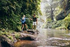 Couples marchant par le courant dans la forêt Photographie stock