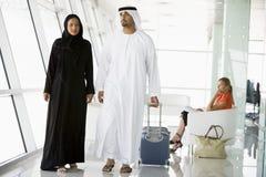Couples marchant par le salon de déviation d'aéroport photo stock