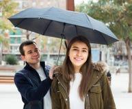 Couples marchant sous le parapluie au jour d'automne Photos stock