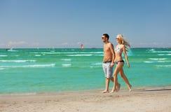 Couples marchant sur la plage Photographie stock libre de droits