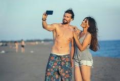 Couples marchant sur la plage au coucher du soleil prenant la photo de selfie sur Mobil Photos stock