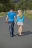 Couples marchant sur la route Photographie stock libre de droits