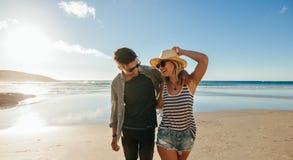 Couples marchant sur le bord de la mer et rire Photographie stock libre de droits