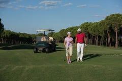 Couples marchant sur le terrain de golf photos stock