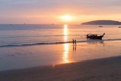 Couples marchant tenant des mains sur la plage au coucher du soleil en Thaïlande, jeune homme de touristes et femme des vacances  Photo libre de droits