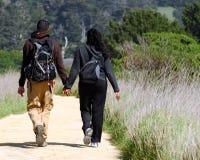Couples marchant un journal Image libre de droits