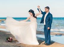 Couples, marié et jeune mariée de mariage dans la robe de mariage près de la mer au bord de la mer photos stock