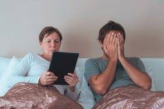 Couples, mari et épouse ennuyés dans la chambre à coucher Photographie stock