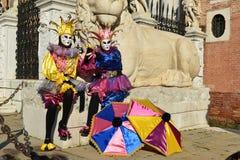 Couples masqués costumés par joker Photographie stock