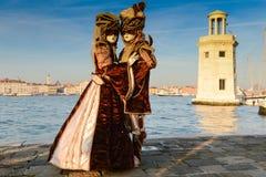 Couples masqués dans des costumes bruns Photos stock