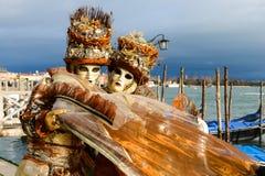 Couples masqués dans des costumes oranges Photographie stock libre de droits