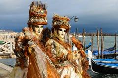 Couples masqués dans des costumes oranges Photo stock