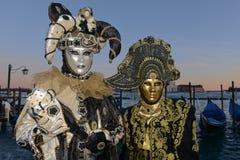 Couples masqués dans le noir et des costumes de carnaval d'or Photos libres de droits