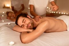 Spouses Relaxing During Couples Massage With Oil At Spa